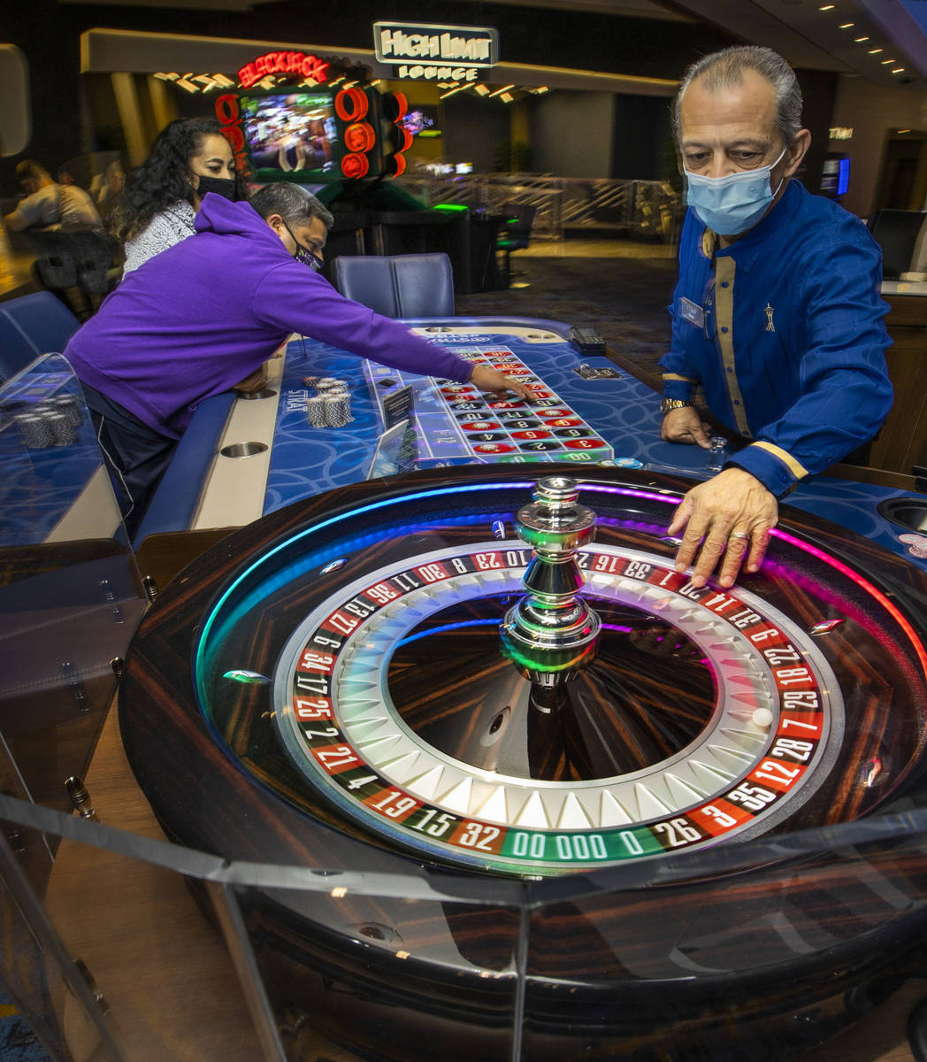 Croupier Mario Dacosta, right, fetches the ball as Marvin Alvarez, center, lays down more chips ...