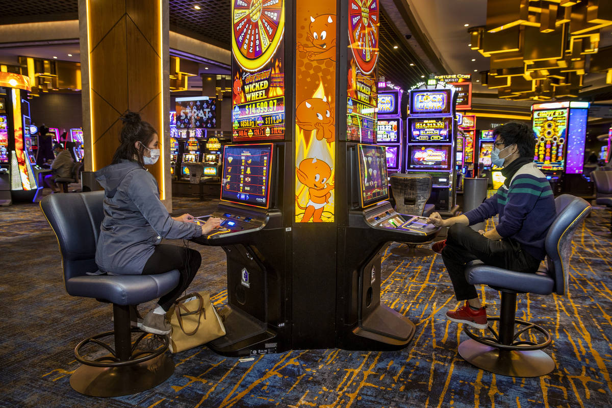 Emily Kluse of Cincinnati, left, and Zaw Naw of Denver play the Hot Stuff Wicked Wheel slots on ...