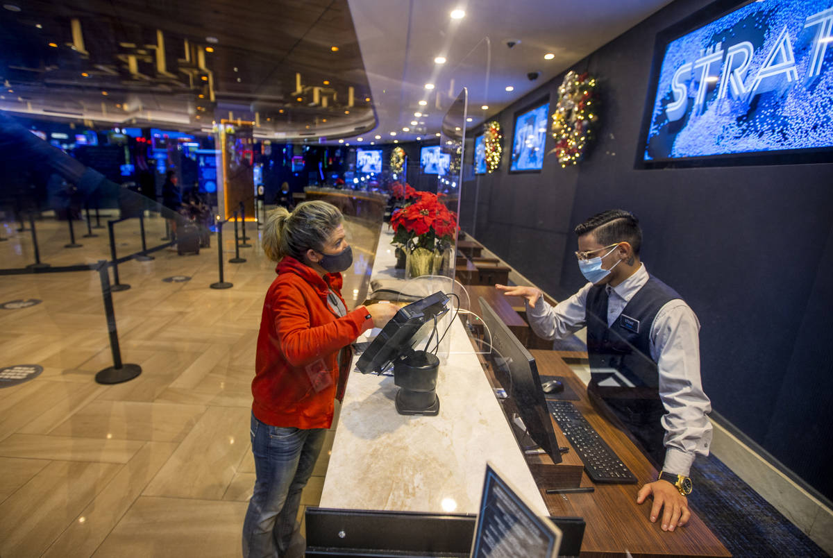Susie Vejvoda of Scottsdale, left, with plexiglass between them, checks into the hotel with the ...