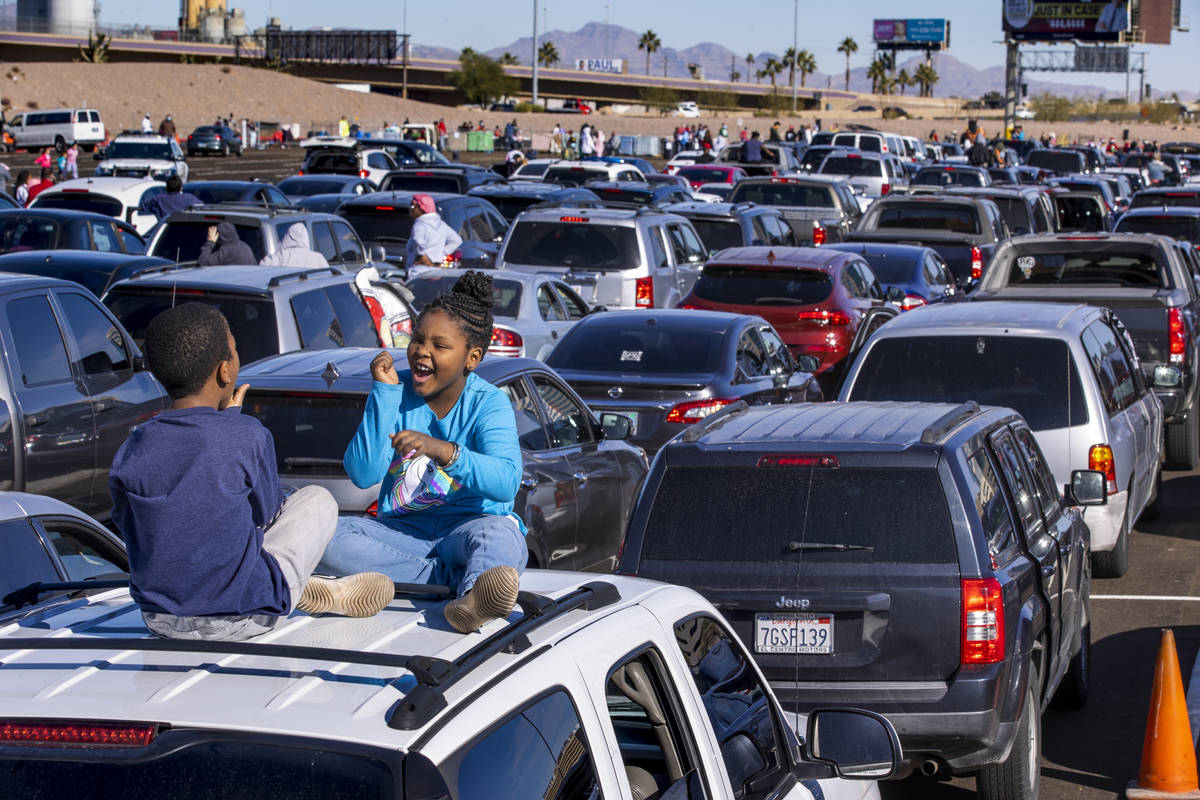 Isaih Brass, 9, and sister Unikiya Brass, 10, play atop their car as hundreds of drivers and pa ...