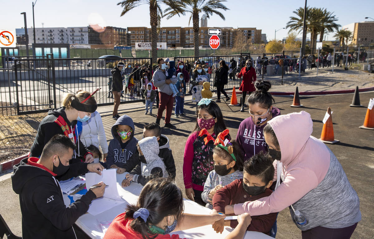 People enter after waiting in line to walk in as the Las Vegas Rescue Mission holds its toy dri ...