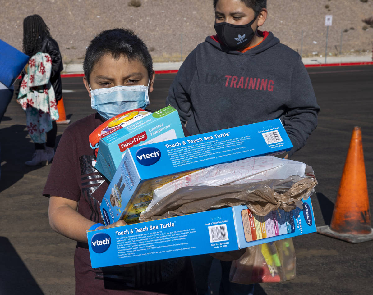 Miguel Geronimo, 8, is loaded with gifts received during the Las Vegas Rescue Mission toy drive ...