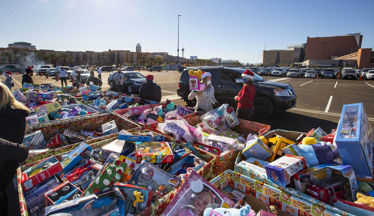 Volunteers greet drivers with toys as the Las Vegas Rescue Mission holds its toy drive on a fir ...