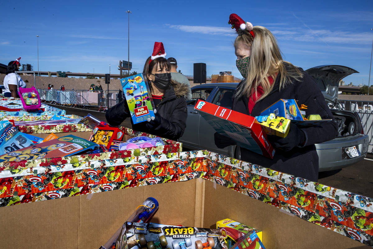 Gina Jones, left, and Patti Dillon grab more gifts to be distributed as the Las Vegas Rescue Mi ...