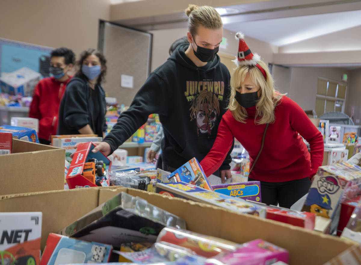 Volunteers Tanner Phillips, 17, left, and Jayme Phillips, 50, of Henderson pack Christmas donat ...