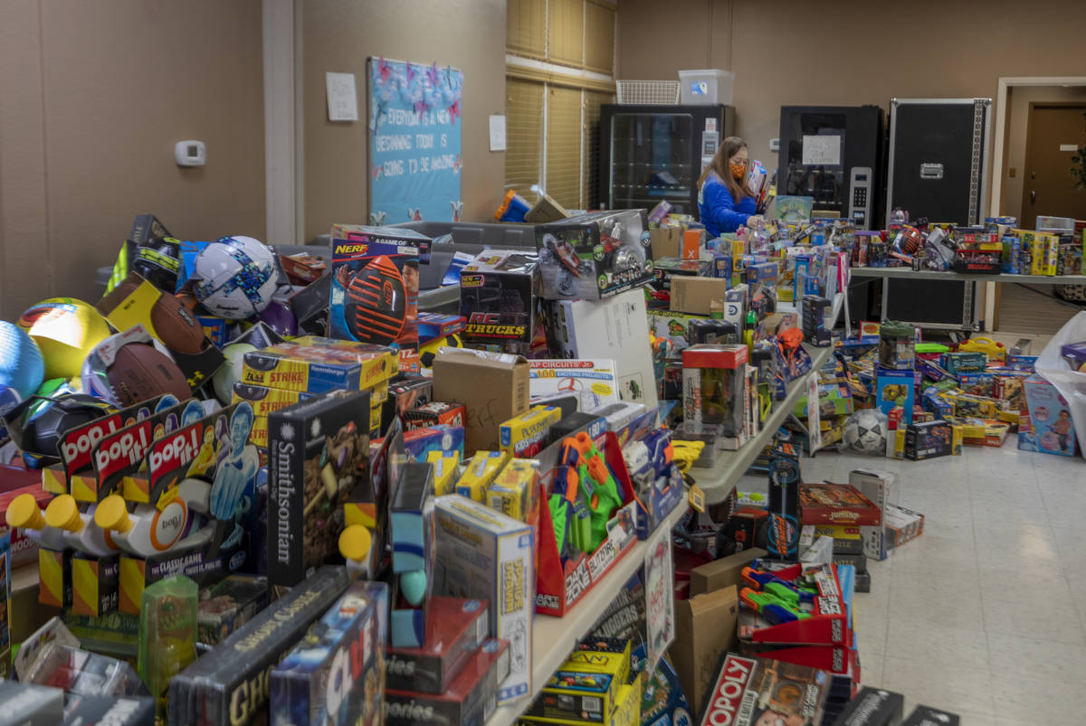 Volunteer Mandisa Alston, of Henderson packs toys for Christmas donations to be given to famili ...