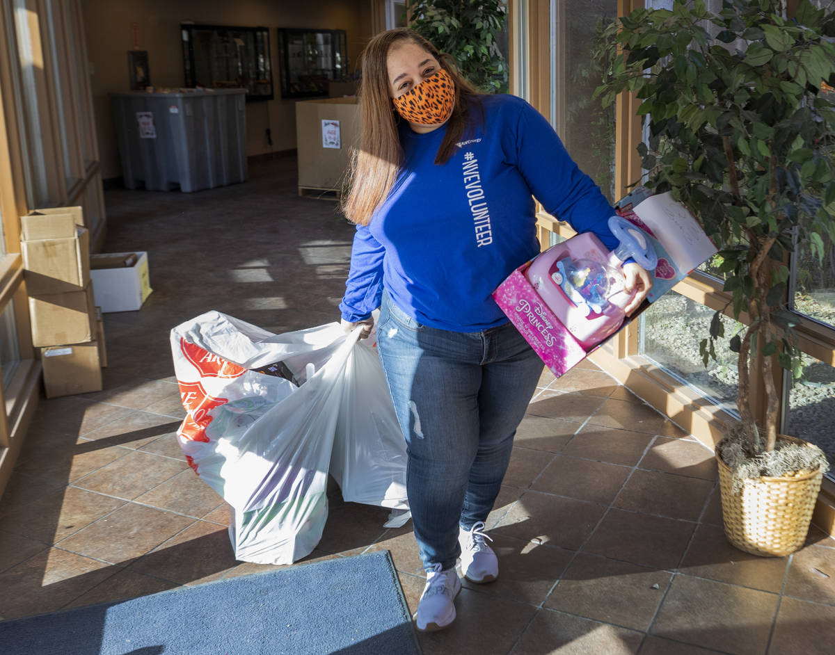 Volunteer Mandisa Alston, of Henderson transfers toys for Christmas donations to be given to fa ...