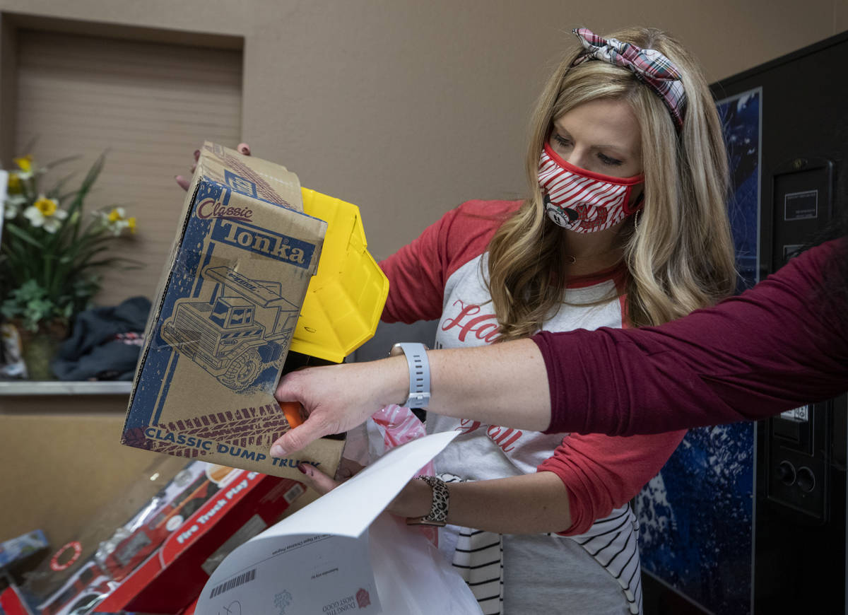 Lacie Jackson, 34, of Las Vegas, packs toys for Christmas donations to be given to families, at ...