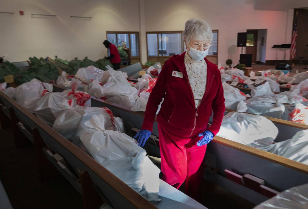 Volunteer Aldona Leskys, 76, of Henderson, organizes individual family Christmas presents, at t ...