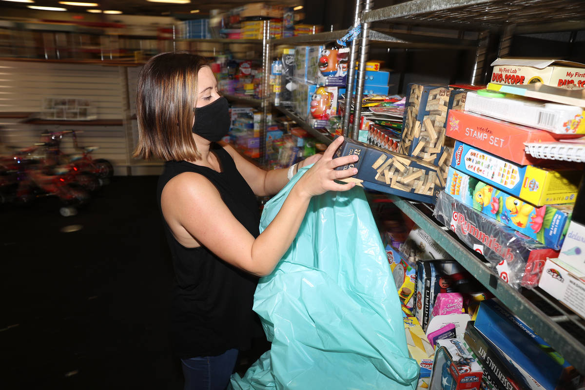 Volunteer Kaila Tuvell makes gift bags during the HELP of Southern Nevada toy drive distributio ...
