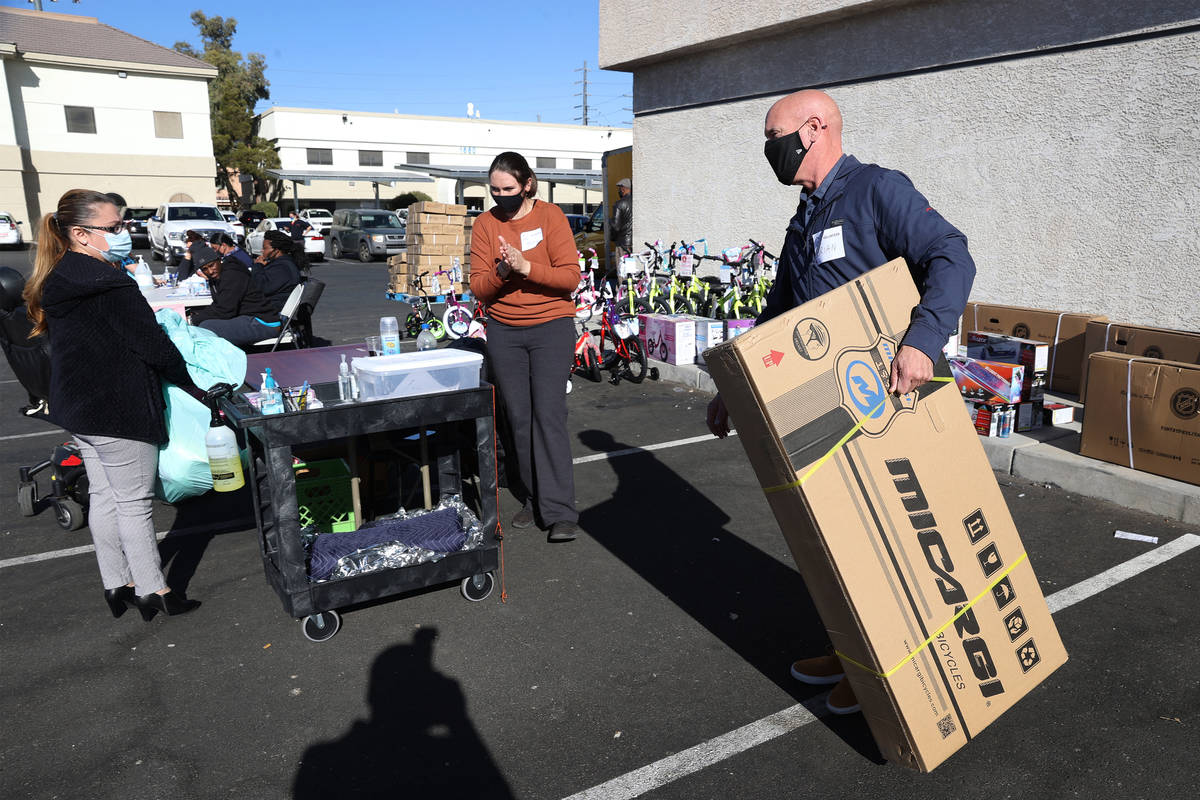 Volunteer Brian McMains, right, delivers a boxed bicycle to a client's vehicle during HELP of S ...