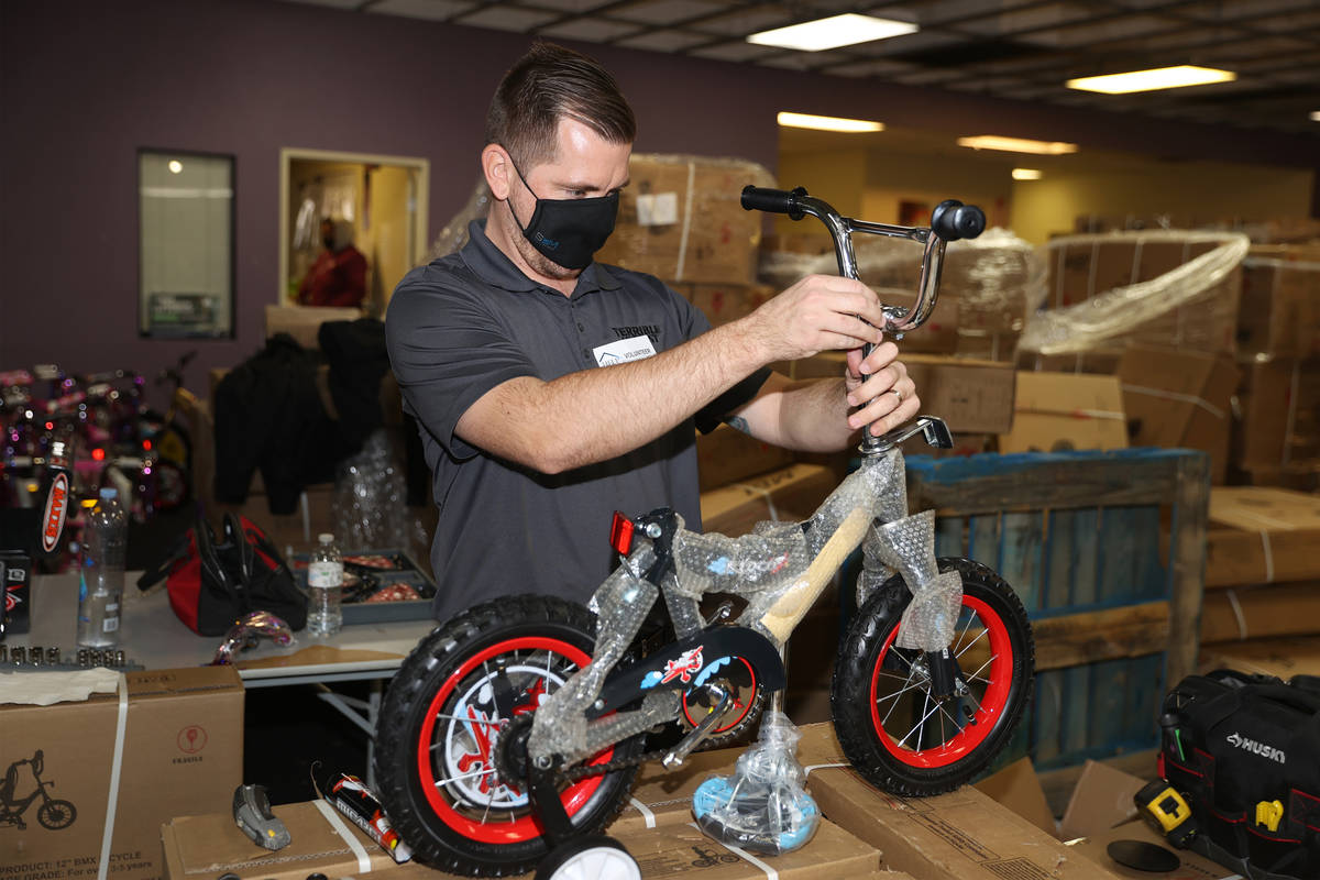 Volunteer Nick Voigt assembles a bicycle for the HELP of Southern Nevada toy drive distribution ...