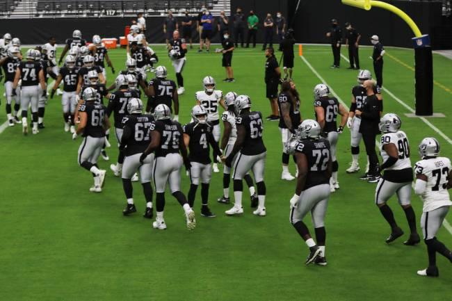 Las Vegas Raiders quarterback Derek Carr (4) greets his teammates as the come through the tunne ...