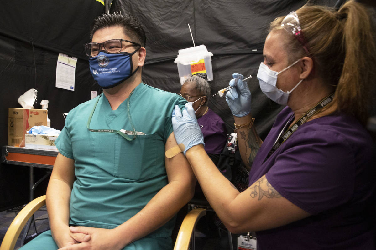 Dr. Myron Kung, left, is given the COVID-19 vaccine by nurse Darlene Roberts at the North Las V ...