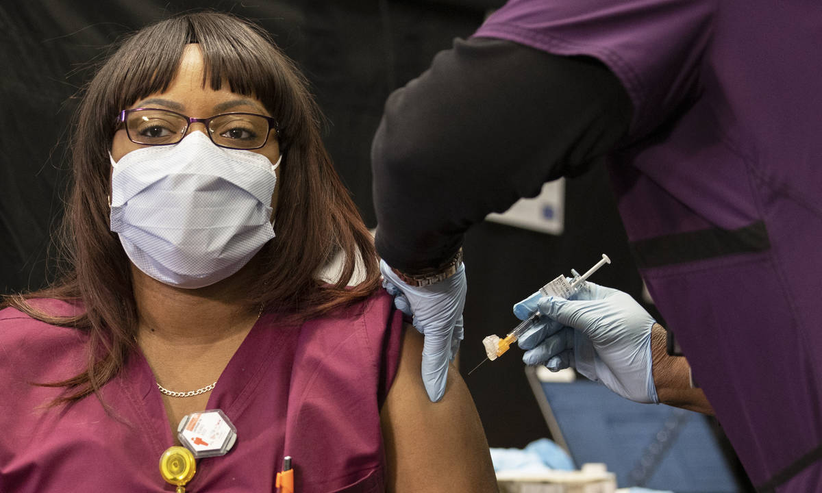 Radiology tech Remiko Ross, left, is given the COVID-19 vaccine by nurse Francine Jones-Toliver ...