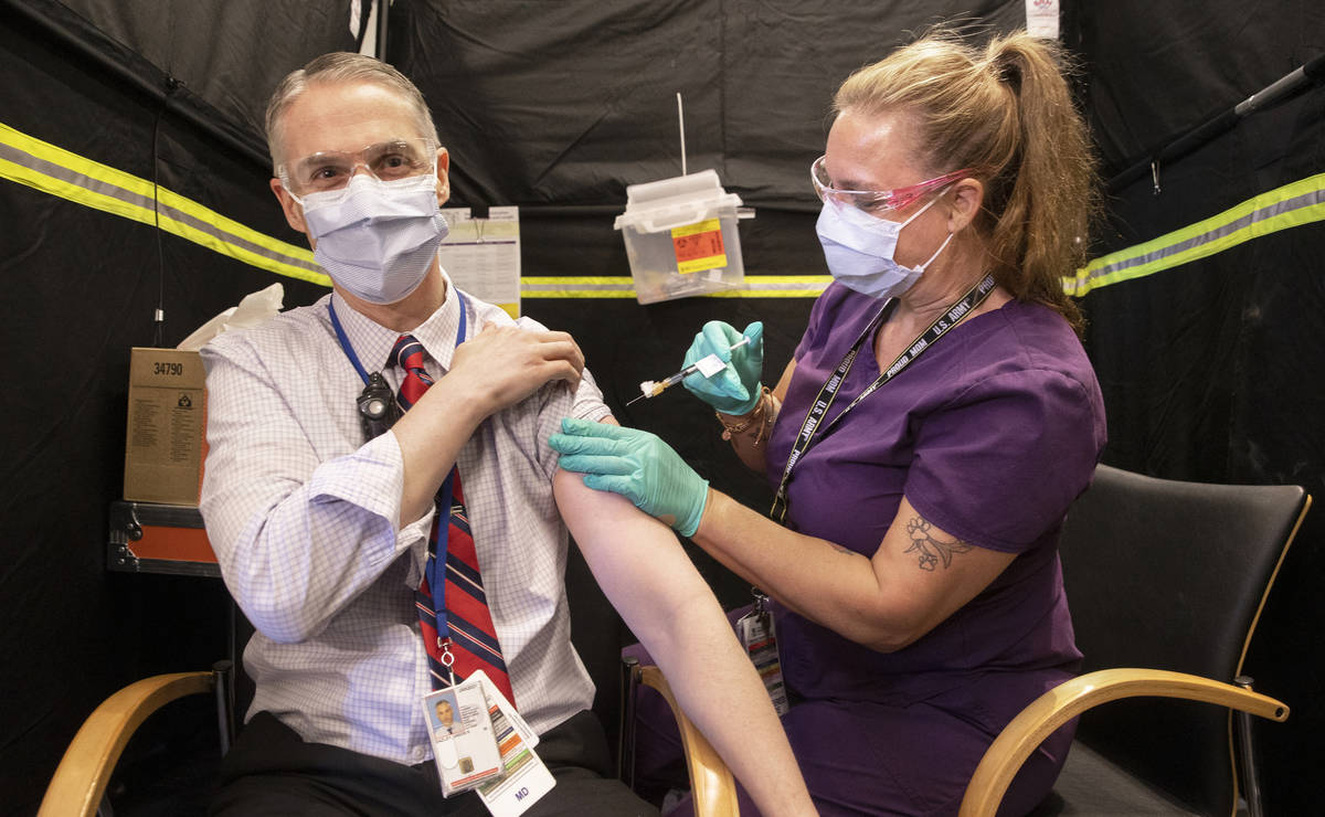 Dr. Jason Dazley, left, is given the COVID-19 vaccine by nurse Darlene Roberts at the North Las ...