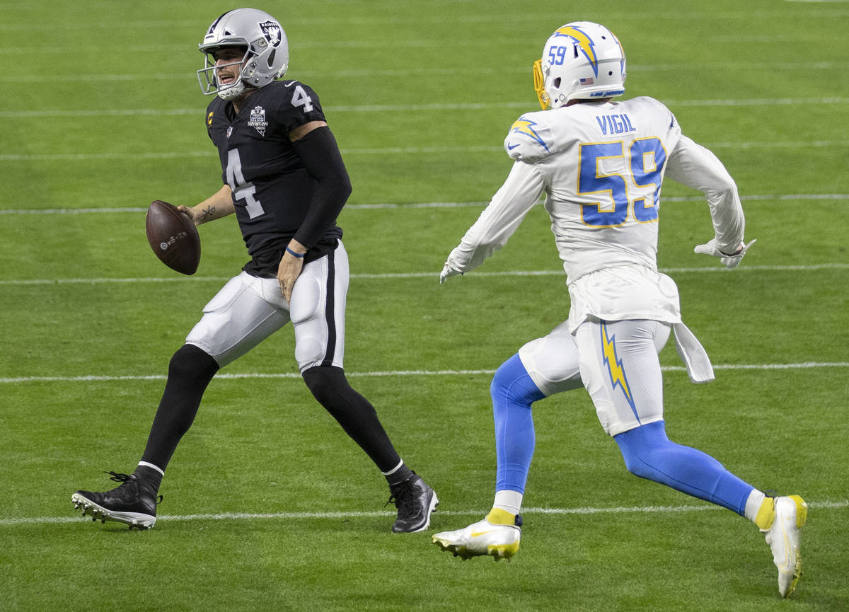 Raiders quarterback Derek Carr (4) winces in pain as he scramble towards the sideline with Los ...