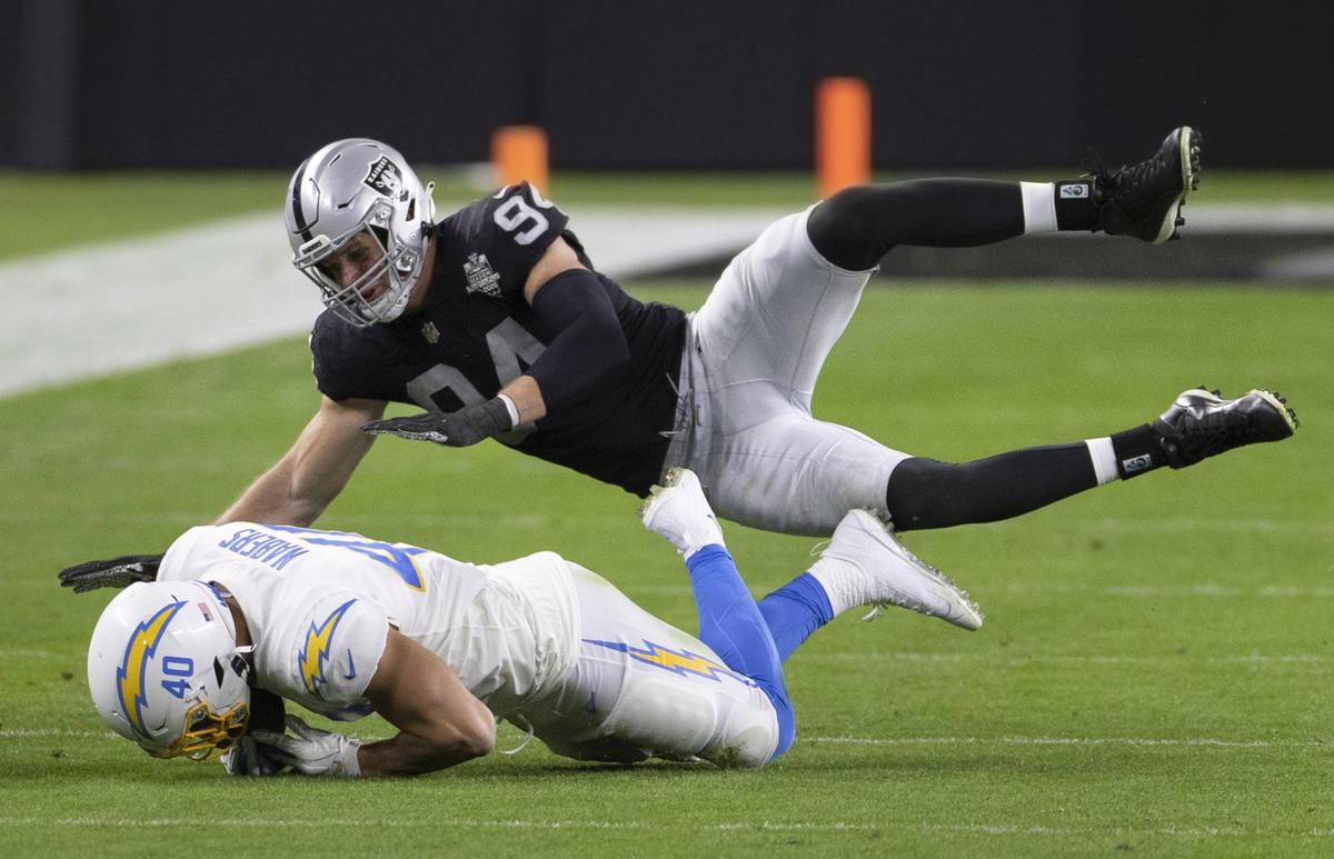 Raiders defensive end Carl Nassib (94) tackles Los Angeles Chargers fullback Gabe Nabers (40) i ...