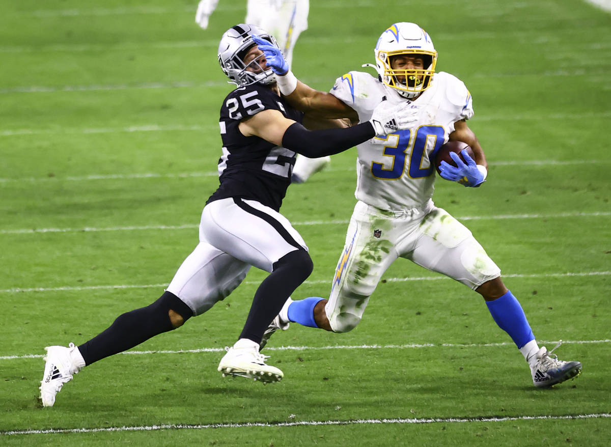 Los Angeles Chargers running back Austin Ekeler (30) runs the ball as Raiders free safety Erik ...