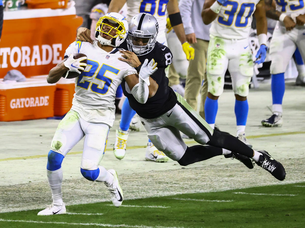 Los Angeles Chargers cornerback Chris Harris (25) gets tackled by Raiders quarterback Marcus Ma ...