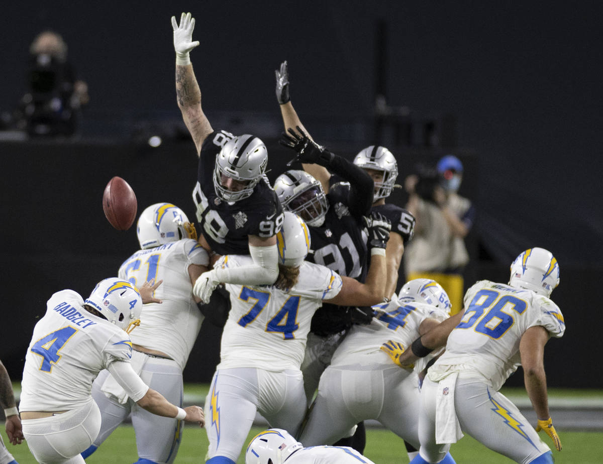 Raiders defensive end Maxx Crosby (98) and Raiders defensive tackle Kendal Vickers (91) leap to ...