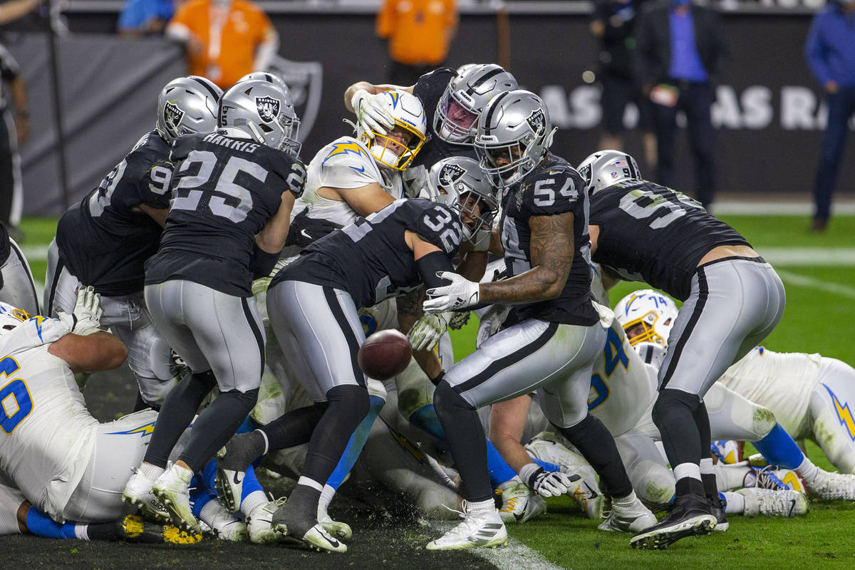 Los Angeles Chargers quarterback Justin Herbert (10) fumbles as he is hit by Raiders inside lin ...