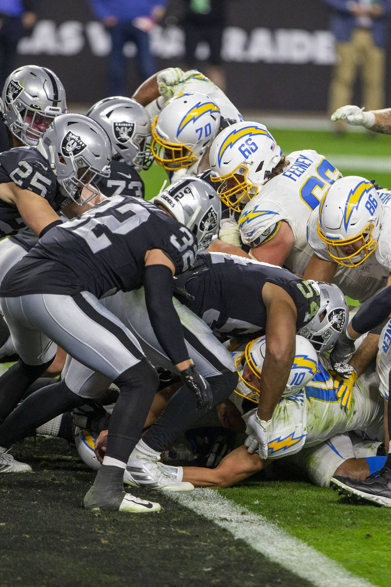 Los Angeles Chargers quarterback Justin Herbert (10) reaches into the end zone to score the gam ...