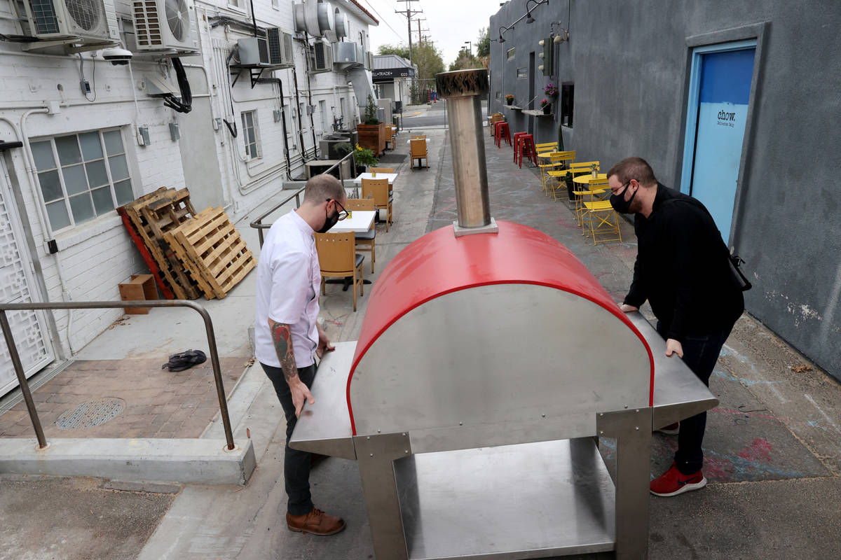 Alex White, left, and Cameron White of Yukon Pizza move their pizza oven at Vegas Test Kitchen ...