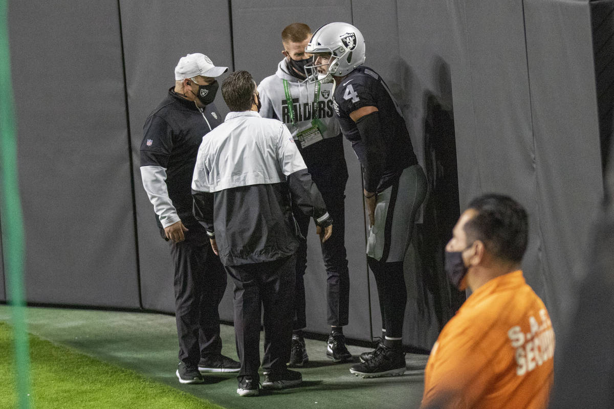 Raiders quarterback Derek Carr (4) is attended to by trainers after injuring his groin on a run ...