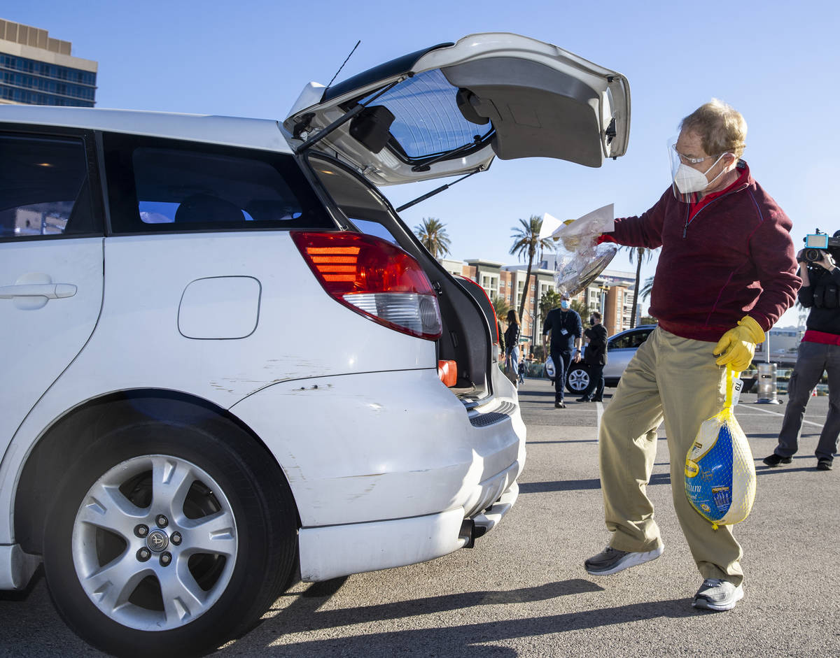 Raymond Teller delivers a turkey and cookies to an awaiting vehicle during the re-opening of th ...
