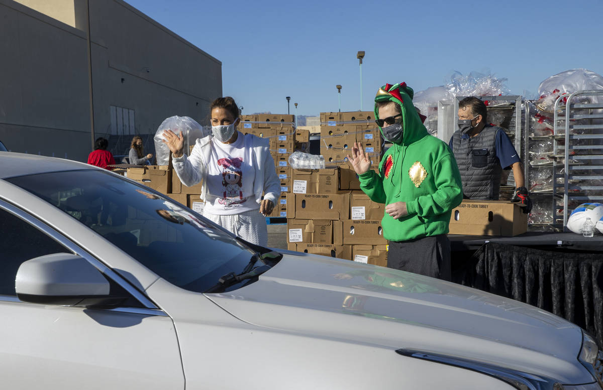 Jade Simone, left, and Piff the Magic Dragon greet another motorist during the re-opening of th ...