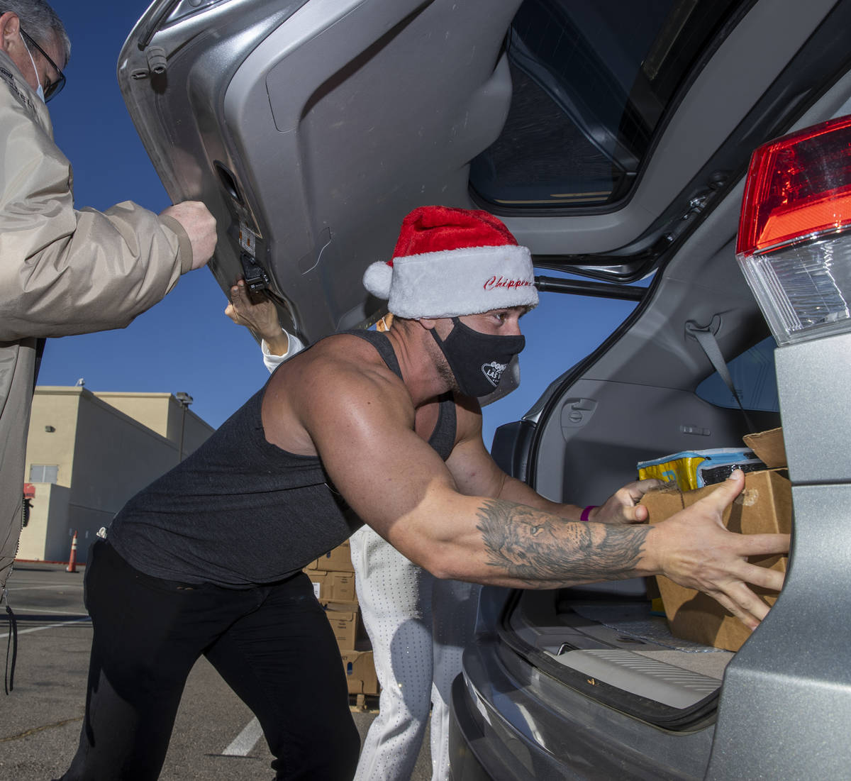 Chippendales member Ryan Worley loads up turkeys and cookies to an awaiting vehicle during the ...