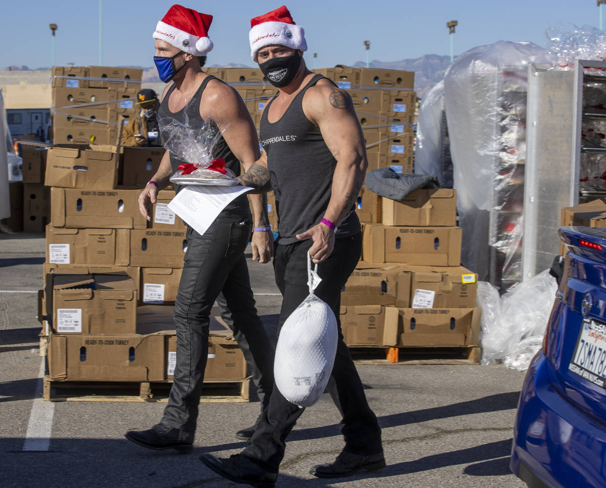 ChippendalesÕ Ryan Kelsey, left, and Ryan Worley deliver turkeys and cookies to awaiting ...
