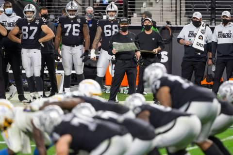 Raiders head coach Jon Gruden, center, watches a play ensue in the fourth quarter during an NFL ...
