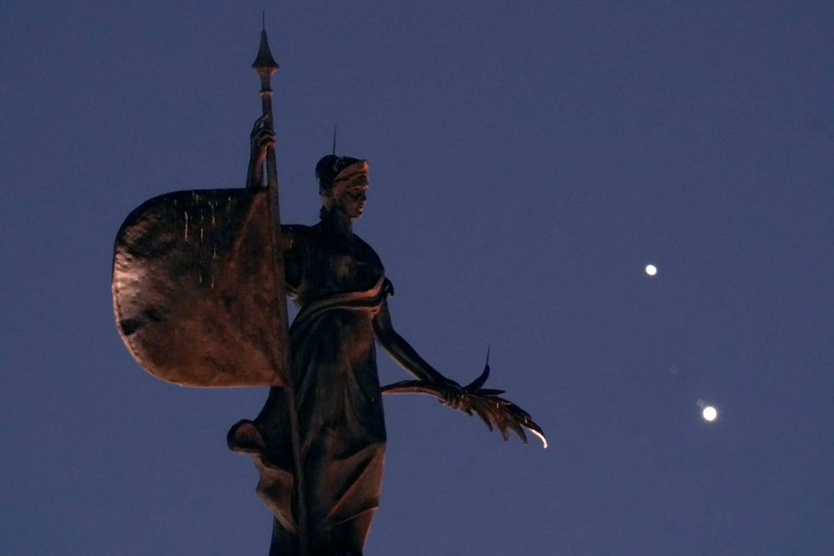 A statue atop a half-scale replica of Seville, Spain's La Giralda Tower stands in the foregroun ...