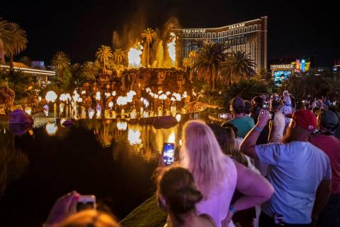 People on the Strip watch the first volcano show since the reopening of the The Mirage earlier ...