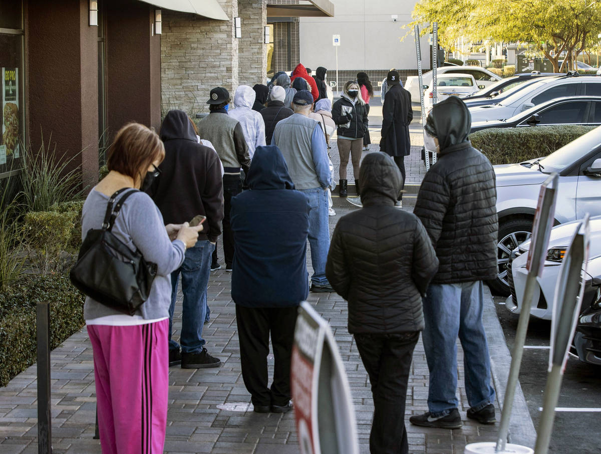People line up outside of CareNow Urgent Care at 7040 South Durango Drive, on Tuesday, Dec. 22, ...