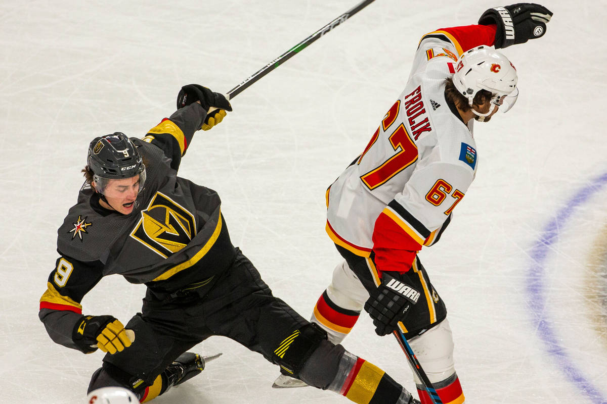 Vegas Golden Knights center Cody Glass (9, left) is takes dow by Calgary Flames right wing Mich ...