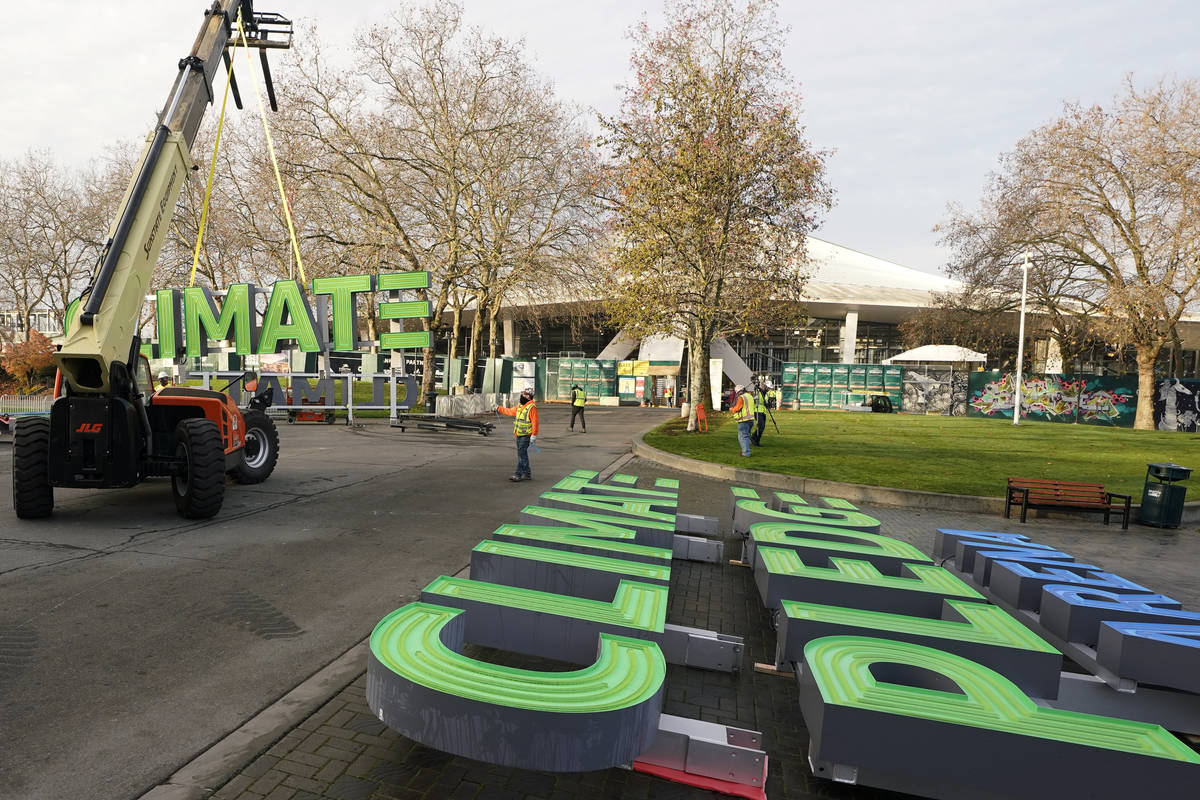 Workers assemble signs for the top of Climate Pledge Arena (shown in the background), the futur ...