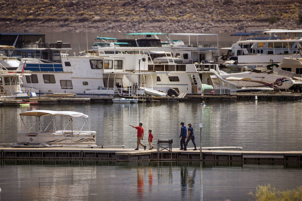 People walk along a dock at the Lake Mead Marina about the Lake Mead National Recreation Area T ...