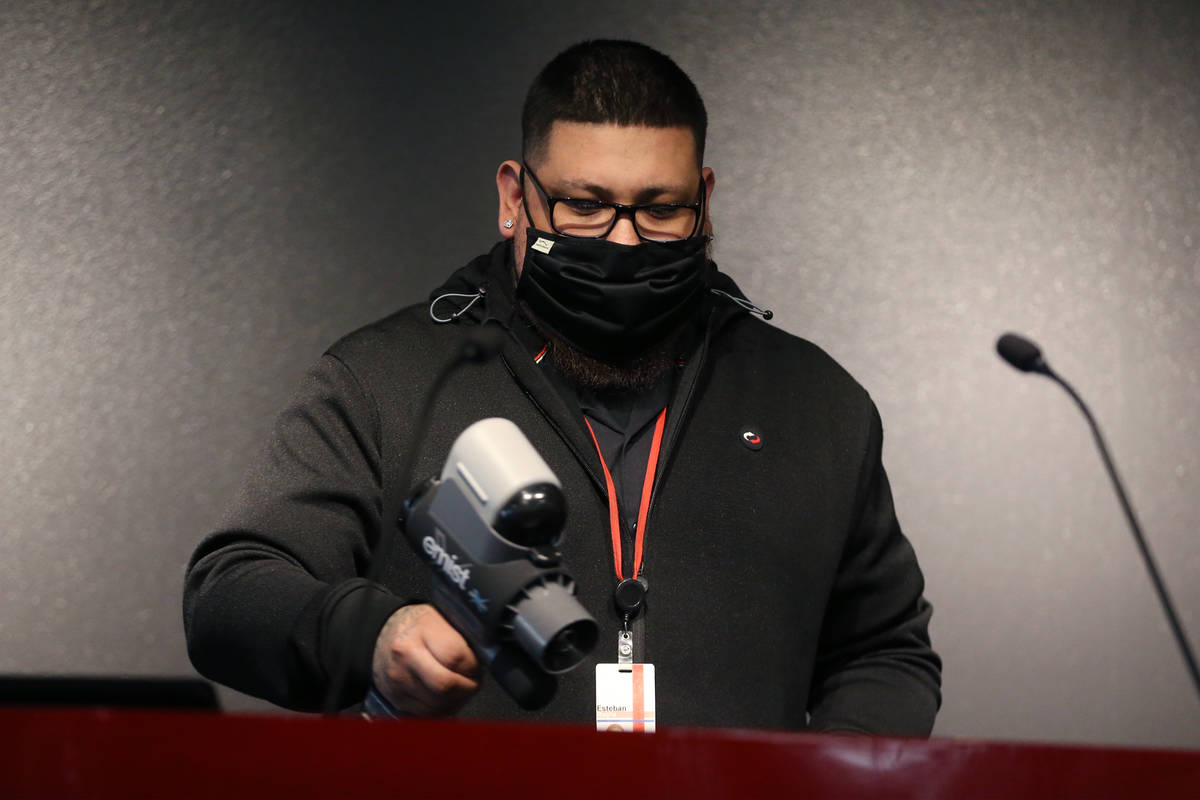 Switch employee Esteban Rocha sanitizes the podium during a press conference to discuss New Yea ...