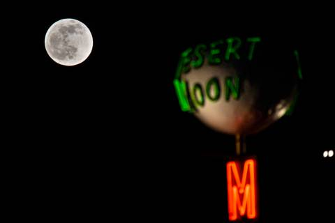 The last full moon of the year rises above the Desert Moon Motel sign on east Fremont Street in ...