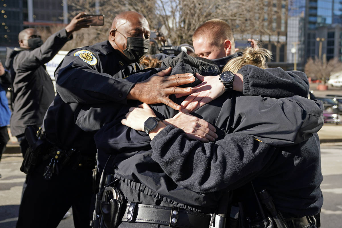 Nashville Police Chief John Drake, left, joins a group of police officers as they embrace after ...
