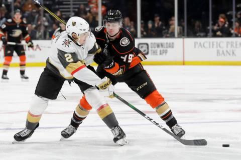 Vegas Golden Knights defenseman Zach Whitecloud, left, passes around Anaheim Ducks left wing Ma ...