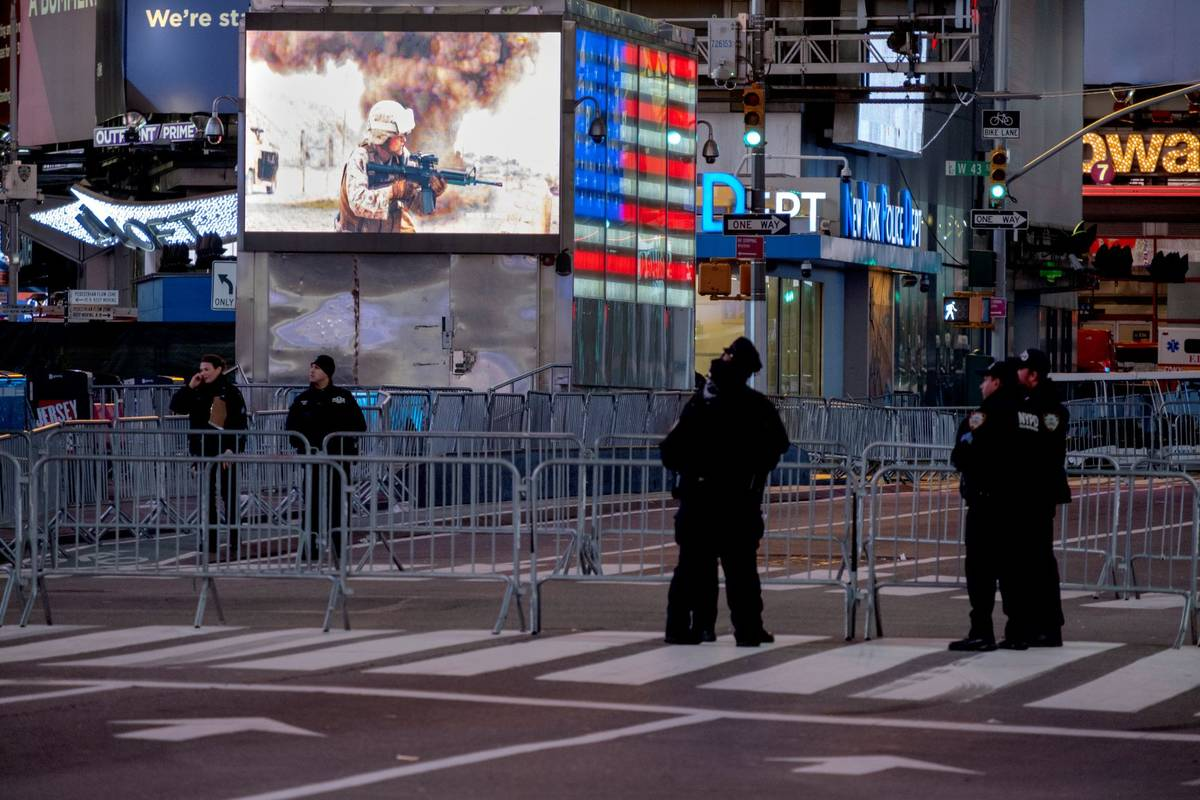 Police officers stand along a mostly empty Seventh Avenue during what would normally be a Times ...