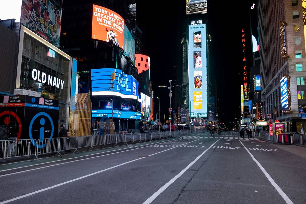 Seventh Avenue is mostly empty during what would normally be a Times Square packed with people, ...