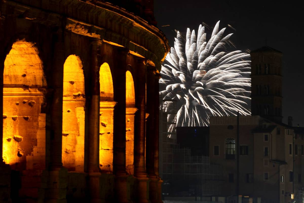 Fireworks explode in the sky next to Rome's Colosseum during New Year's celebrations, in Rome, ...