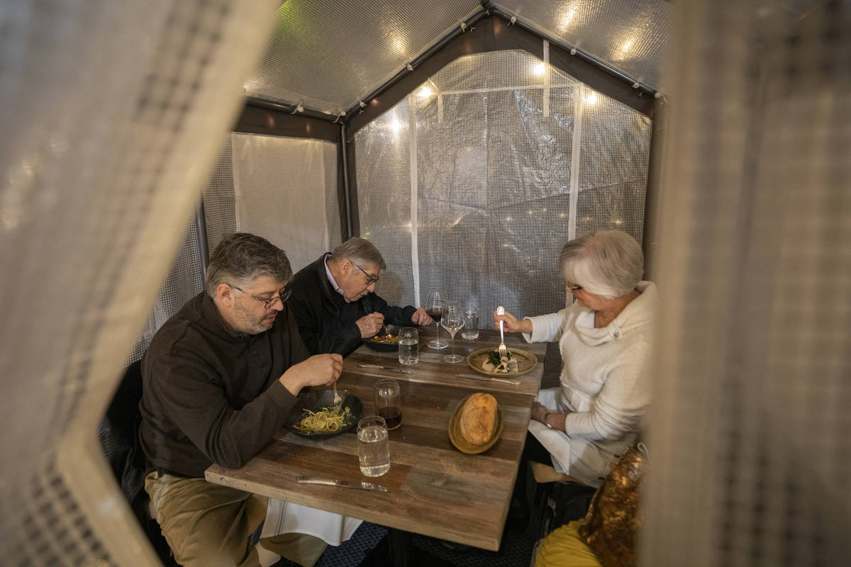 Adam Winer, left, Howard Winer, center, and Charlotte Winer dine in a dining tent outside of Es ...