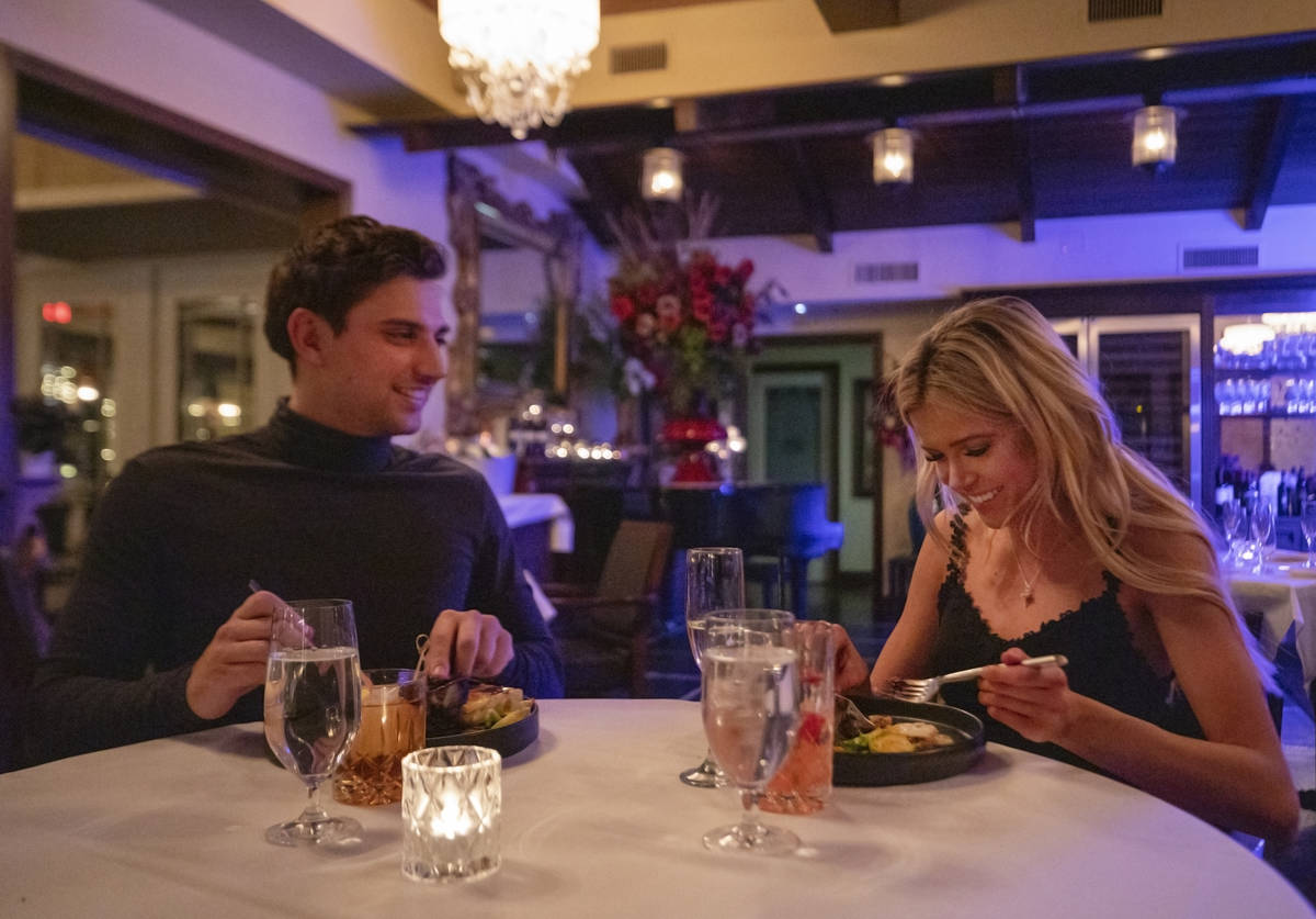 Jesse Neely, 23, of Las Vegas, left, and Taylor DeRose, 23, of North Las Vegas, dine at America ...