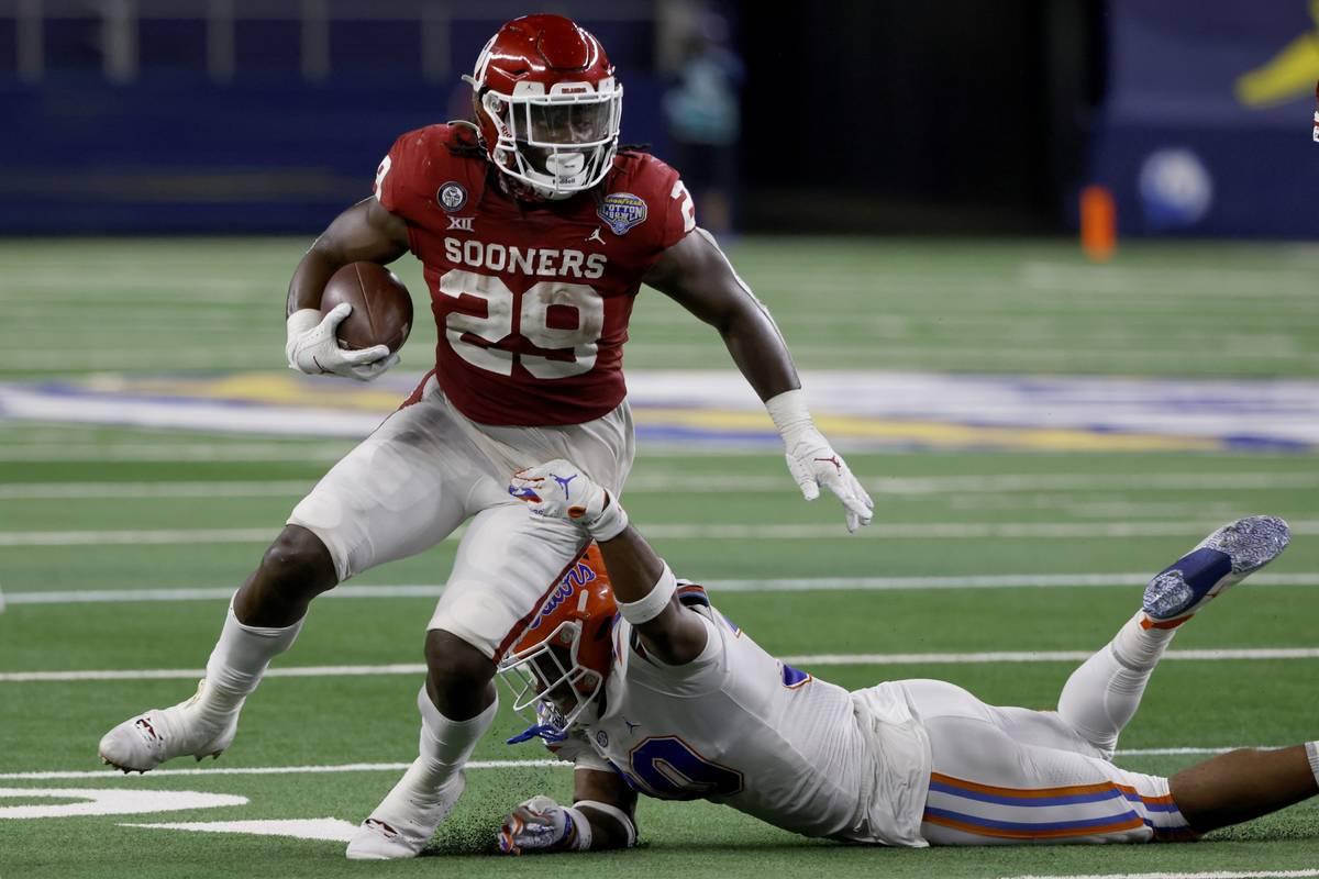 Oklahoma running back Rhamondre Stevenson (29) breaks a tackle attempt by Florida linebacker Am ...